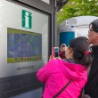 Asian tourists near interactive information scoreboard in the street of Vilnius — Stock Photo #68408665