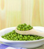 A wooden spoonful of fresh green peas — Stock Photo