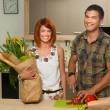 Happy couplestanding in kitchen and cooking — Stock Photo #53373765