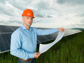 Man holding solar panel station plans — Stock Photo