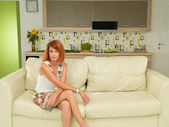 Woman sitting on a couch, relaxed — ストック写真