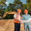 Engineer discussing plan with construction worker — Foto Stock #54885021
