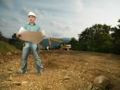 Male architect reading blueprint on worksite — Stock Photo