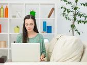 Bella donna usando il portatile sul divano — Foto Stock