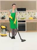 Woman vacuuming kitchen floor — Stock Photo