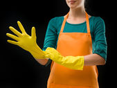 Cleaning lady putting on rubber gloves — Stock Photo