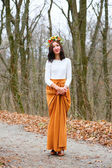 Young beautiful woman with flower wreath in autumn outdoors — Stock Photo