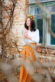 Young girl with flower wreath on her head near window — Stock Photo