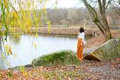 Autumn young girl near the pond — Stok fotoğraf