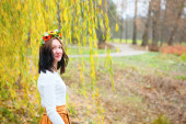 Vacker flicka med blomma krans i höst park — Stockfoto