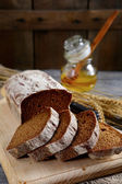 Bread sliced into pieces and honey on the cutting board — Stockfoto