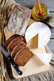 Black bread with brie cheese on a cutting board — ストック写真