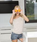 Funny blond girl doing orange glasses  — 图库照片