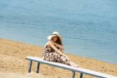 Sweet girl on beach with hat resting — Stock Photo