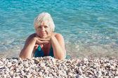 Sahilde yatan kadın kıdemli — Stok fotoğraf