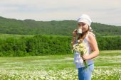 Kid girl with  flowers and glass of milk on the meadow — Stock Photo