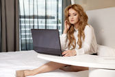 Businesswoman using laptop while lying on bed — Stock Photo