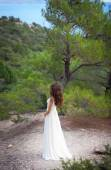 Beautiful girl wearing white flowy dress in forest — Stock Photo