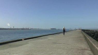 Man is walking on breakwater — Stock Video