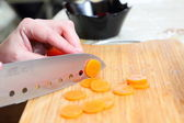 Chefs hands chopping carrot — Stock Photo