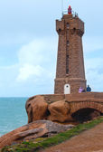 Ploumanach lighthouse and family near.The Pink Granite Coast. — Stock Photo