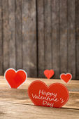 Red Valentine hearts on old rustic wooden background — Stock Photo