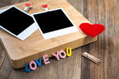 Two blank instant photos with red hearts.On wooden background — Foto Stock