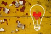 Drawing love symbol in light bulb on old wooden wall — Foto Stock
