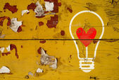 Drawing love symbol in light bulb on old wooden wall — Stockfoto
