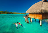 Young couple snorkling from hut over tropical lagoon — Stockfoto