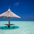 Bamboo beach umbrella with bar seats in the water — Stock Photo #64181053