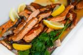 Stakes from a salmon with lemon on a plate — Stock Photo