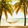 Hammock between two palm trees on the beach during sunset, cross — Stock Photo #70536787