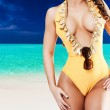 Sexy woman in yellow bikini in front of tropical beach with blue — Stock Photo #70536919