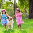 Young girls running with a golden retriever — Stock Photo #78985656