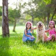 Little girls and dog in the park — Stock Photo #78985668