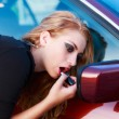 Cute blond putting lipstick on using the car mirror — Stock Photo #53386473