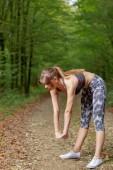 Piękna młoda kobieta robi ćwiczenia rozciągające na drodze leśnej — Zdjęcie stockowe