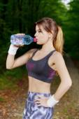 Attractive sporty woman drinking water from a bottle after joggi — Foto de Stock