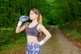 Attractive sporty woman drinking water from a bottle after joggi — Zdjęcie stockowe