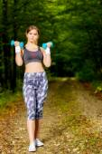 Beautiful young woman doing stretching exercise on road forest — Stock Photo