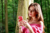 Young beautiful woman with toothy smile send a text message vie  — Stock Photo