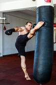 Kickboxer training in the gym kicking the punch bag — Stock Photo