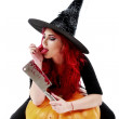 Witch with bloodstained hands with a hatchet in hand sits on a p — Stock Photo #55356471