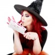 Witch with bloodstained hands with a hatchet in hand sits on a p — Stock Photo #55356515
