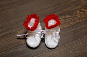 Baby's bootee on wooden background — Stock Photo