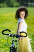 Beautiful young woman with a bicycle in nature — Φωτογραφία Αρχείου