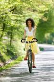 Young beautiful woman riding a bicycle in a park. Active people. — Stock Photo
