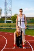 Joven pareja en posición preparado para competir el deporte y — Foto de Stock