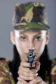 Female soldier in camouflage uniform with weapon isolated on gray background — Stock Photo